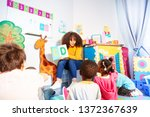 kids sit around teacher and... | Shutterstock . vector #1372367639