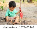 child are digging the soil by... | Shutterstock . vector #1372459460
