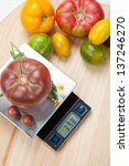 Digital kitchen scale on table surrounded with fresh tomatoes, and basil. - stock photo