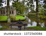 man in a bench in front ... | Shutterstock . vector #1372560086