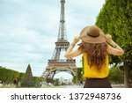 Small photo of Seen from behind stylish solo tourist woman in yellow blouse and hat in Paris, France sightseeing.