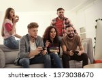 emotional friends playing video ... | Shutterstock . vector #1373038670