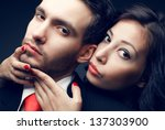 Portrait of a sexy couple, beautiful young man and woman posing over dark blue background. Classic style. Perfect hair and skin. Close up. Studio shot. - stock photo