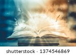 Small photo of Imagine a picture book of an ancient book opened on a wooden table with a sparkling golden background. With magical power. magic. lightning around a glowing glowing book In the room of darkness