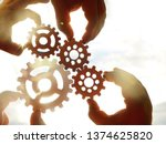 Small photo of Male hands holding four 4 wooden cog wheels, gear wheels on sunny sky background. family concept.