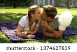 Stock photo teenagers kissing lying on plaid in park holding cotton candy romantic date 1374627839