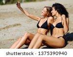 two women taking selfie... | Shutterstock . vector #1375390940