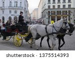 Small photo of Vienna, Austria - 04/08/2019: Chaise with passangers and cabby driving through streets of Vienna.