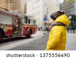 little boy looks on fire engine.... | Shutterstock . vector #1375556690