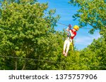 Small photo of Little brave caucasian 7 years old girlie using a zip line in a rope playground structure in 5 meters high altitude.