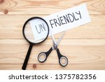 Small photo of Paper with word Unfriendly, scissors and magnifying glass on wooden table