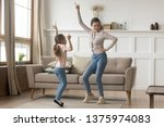 Small photo of Active family young mother dance having fun with little preschool or school age daughter older younger sister listens happy song moving together, leisure activities with kid positive emotions concept