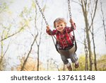 A Young Toddler Boy Swinging I...