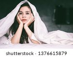 Small photo of sleepless Asian woman lying down on bed tired from insomnia