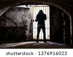 Small photo of Prisoner man locked up standing in old underground cellar , silhouette from behind against bars - Captive inside dark basement in desperate isolation feeling - Concept of denial human rights - Image