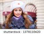 Russian beauty. Portrait of a young beautiful girl in a white hat with a fur hat against a red square in Moscow