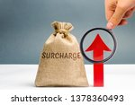Small photo of A cash bag with the word Surcharge and a red up arrow. Increase in fine and penalties for violating. The system of cumulative penalties. Progressive system. Evaluation of the effectiveness of fines.