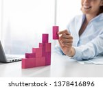 Smiling businesswoman building a successful financial chart using wooden pieces, she is adding the last block - stock photo