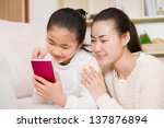 mother and daughter using a... | Shutterstock . vector #137876894