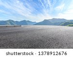 Parking lot pavement and green mountains natural landscape under the blue sky - stock photo