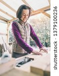 a woman works in a carpentry... | Shutterstock . vector #1379100236