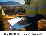Small photo of Miner supervisor checking site emergency phone number before sigh of confined space permit prior to performing high risk work on construction mine site, Perth, Australia