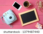 Modern polaroid camera, photo frame, cup of coffee, gift, flowers on rustic pink wooden background. Top view, tender minimal flat lay style composition. Women desk, fashion blogger, beauty technology