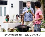 Two men toasting beers by the barbeque at a party, with meat on the smoking grill - stock photo
