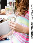 Woman hand holding champagne glass flute during outdoor party - stock photo