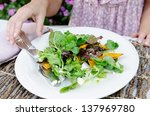 Close up of woman eating healthy green raw salad, alfresco dining - stock photo