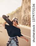 Small photo of Young hipster girl posing with longboard, skateboard, street photo, life style, freedom, happy face,Beautiful young girl with tattoos riding longboard in sunny weather,Bali,cap,glasses, sneakers, road