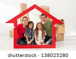 Family with kids portrait in their new home - with cardboard boxes and house shaped frame - stock photo