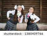 two schoolgirls are holding... | Shutterstock . vector #1380409766