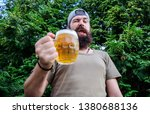 In playful mood. Brutal hipster with winking face having craft beer. Man drinker holding beer mug. Bearded man enjoy drinking beer on nature. Fun loving beer.