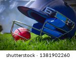 Small photo of Cricket halmet and a ball on a green grass. Helmet protects batsman from fast balls which may otherwise cause harm to playing person.
