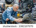 mature repairman with laptop.... | Shutterstock . vector #1382107070