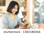 smiling asian woman hold a... | Shutterstock . vector #1382180366