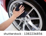 BANGKOK, THAILAND - APRIL 19, 2019: Man's hand cleaning wheel and drying Porsche Cayman with microfiber cloth. Hand wipe down inside shiny rims surface of sportscar. Car detailing and car wash concept - stock photo