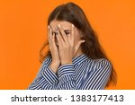 Stock photo scared young caucasian female hiding her fear behind hands portrait of shy timid or ashamed 1383177413