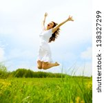 Happy Young Woman Jumping Over...