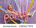 Small photo of Positive Caucasian woman with light hair, poses in shopping cart with colorful modeling balloons, being in good mood, celebrates anniversary, organises noisy bash, isolated over purple background