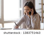 Small photo of Smiling millennial girl distracted from studying at laptop talk chat over phone drawing in notebook, happy young woman sit at office table having pleasant cellphone conversation, female flirt on cell