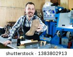 worker showing fixed shoes in... | Shutterstock . vector #1383802913