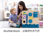 Small photo of Child boy with teacher playing educational toys, stacking and arranging colorful pieces. Learning through experience concept, gross and fine motor skills.
