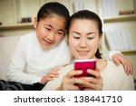 mother and daughter using a... | Shutterstock . vector #138441710