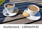 two cups of alfresco coffee... | Shutterstock . vector #1384669433