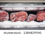 Small photo of Big chunks of red beef lying on the freezer shelves with a big quantity of frozen ice and snow. This freezer hasn't been thawed in a long time.