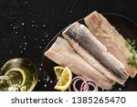 Stock photo marinated fillet mackerel or fillet herring fish with spices greens and slice of bread on plate 1385265470
