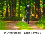 Stock photo girl running with dog outdoors in nature on a path in forest sunny day countryside copy space for 1385759519
