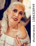 Small photo of Showing tattoo underneath. Languid long-haired old woman having tied hair pointing on her stars tattoo